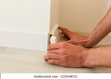 Mans hands putting white baseboard