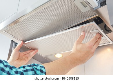 Mans hands removing a filter from cooker hood for cleaning or service. Replacing filter in kitchen hood. Modern kitchen fan or range hood.