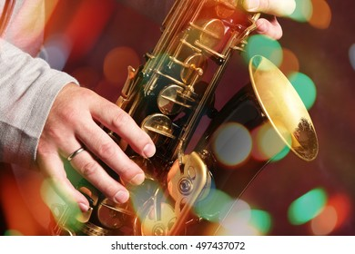Man's hands with saxophone on bokeh lights