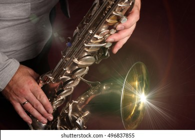 Man's hands with saxophone on burgundy background