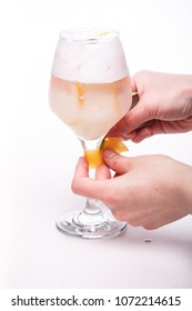 man's hands serving a creamy cocktail with orange at wineglass