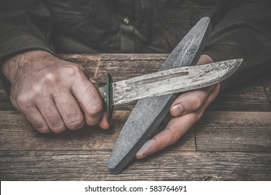 Man's hands sharpening old knife on the wooden table. Dark, vintage atmosphere.