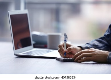 Man's hands taking notes and using laptop at the table