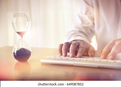 Man's hands typing on computer keyboard next to a hourglass. Concept of time management, business schedule and deadline, for background, website banner, promotional materials, advertising.