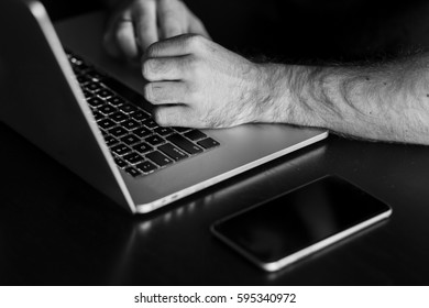 Man's hands are typing something on the laptop. Black and white photo