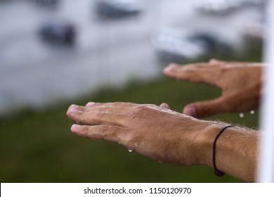 man's hands under rain