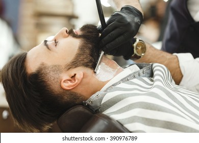 Man's hands wearing black gloves and watch making a beard form with razor for man with dark hair and beard at barber shop, portrait, close up.