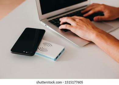 Man's hands working on laptop, wireless powerbank charging phone