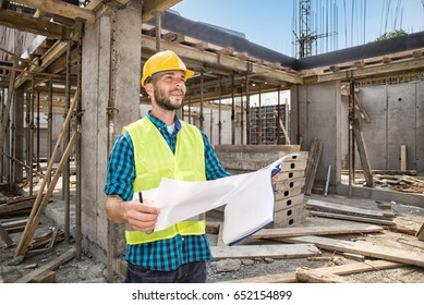 Mans in hardhat and green jacket posing on building site.Film noise