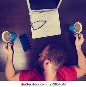mans head down on a tabletop while holding two cups of coffee while working at a desk on laptop with an instagram filter