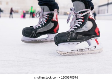 Man's hockey skates on ice background. People skate on the rink. Weekend entertainment in the winter outdoors.