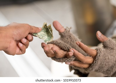Man's holding money gives money to a homeless person. Senior person hands begging for money