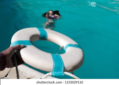 Man's holding out a life preserver out to save a Caucasian woman with dark hair from drowning in a swimming pool. Cry for help man tries to save a woman who can't swim. Girl drowning in pool.