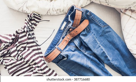 Man's jeans laid on bed in the morning light with strip t-shirt.