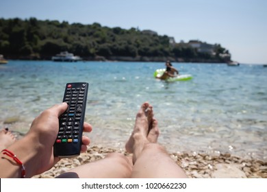 Man's leg on the beach. Man with TV remote control. Summer success life. Live your dream. Summer inspiration
