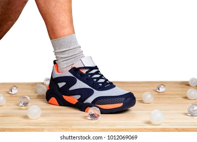 A man's leg, shod in sporting sneakers on a wooden plank floor with a white background