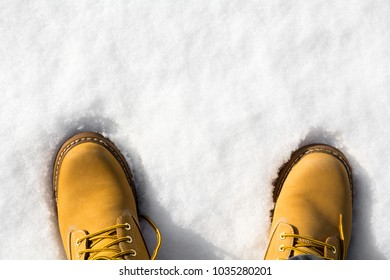Man's legs in brown boots in snow