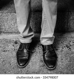 A man's legs and feet wearing worn in cap toe shoes outside a doorstep on a New York City street. Grunge black and white filter applied.