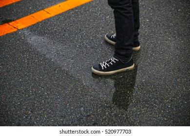 Man's legs in jeans and sneakers on the wet street.  - Shutterstock ID 520977703