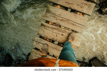 Man's legs on an old wooden bridge through the river