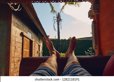 Man's legs on a porch sofa in summertime.