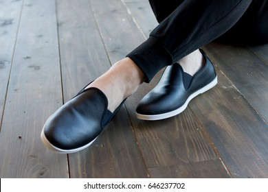 Mans legs wearing jeans and sneaker, casual shoes, black leather new modern casual summer shoes for men, moccasins.