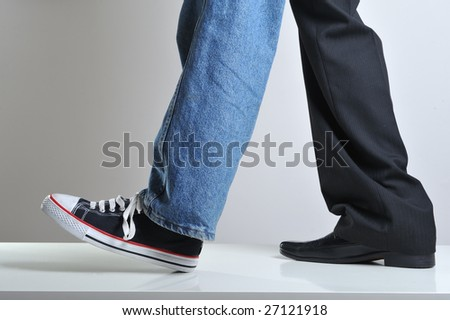 Mans legs wearing jeans and sneaker on a leg and suit on the other