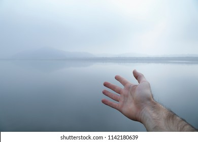 A man's outstretched hand reaching to a open landscape on a misty river.