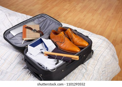 Man's packed open black suitcase on top of a bed