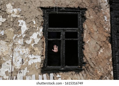 Man's palm in an old black wooden charred window without a glass of an abandoned old house. Mystical and horror background.