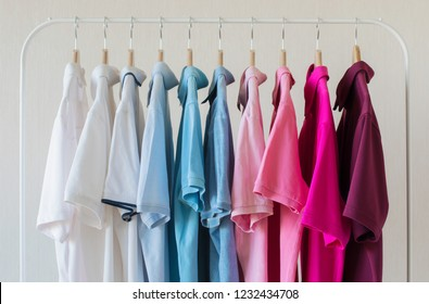 Man's polo shirts hanging in row in rack