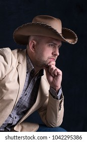 The man's portrait in a cowboy's hat. He sits in a jacket and jeans and thinks. The young man sits on dark background in studuo.