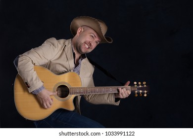 The man's portrait in a cowboy's hat on dark background in studio.  He sits in a shirt and jeans and looking aside. He plays the guitar and sings.