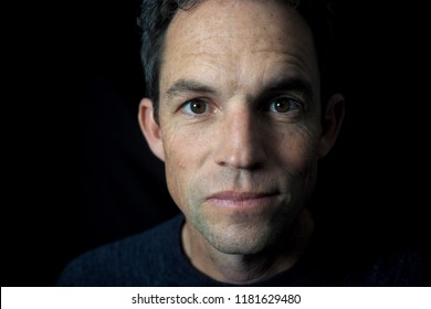Man's portrait with dramatic light, black background