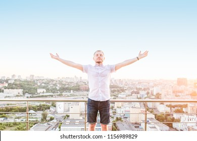 Man's portrait on a high rise building balcony overlooking city with hands rised up to sky, feeling and celebrating freedom, victory, sucsess. Expressing his joy of life. Positive emotion. Copy space