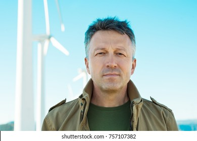 Man's portrait outdoor against the industrial landscape with wind turbines