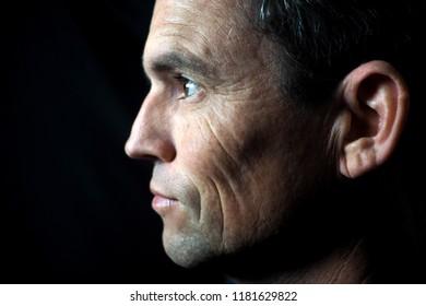 Man's portrait in profile, black background