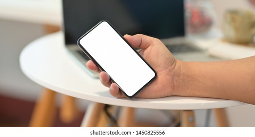 Man's right hand holding smartphone with blank screen in his office