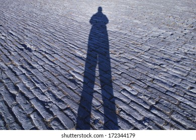 Man's shadow on the ancient brick ground, photoed in Forbidden City