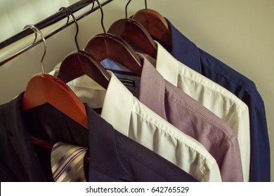 Man's shirts and jacket hanging on hangs. Man's wardrobe. Office style.