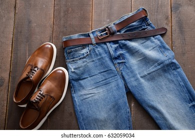 Mans shoes and blue jeans ,belt on wood background