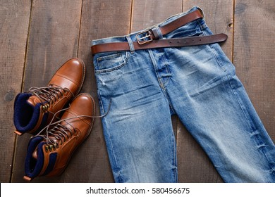 Mans shoes and blue jeans on wood background
