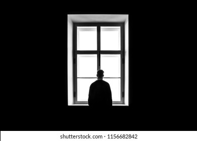 A man's silhouette in front of the window. Black and white. Concept of loneliness and isolation.