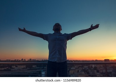 Man's silhouette with hands rised up to sky on sunset cityscape bacground. Feeling and celebrating freedom, victory, sucsess. Expressing joy of life. Positive emotion. Selective focus. Copy space