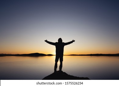 Man's silhouette stands with raised arms against sunset lake and mountains