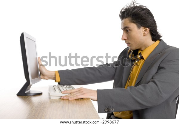 Man's sitting at the desk. There's computer on it. Wind's blowing from LCD screen and man's holding it. Isolated on white in studio.
