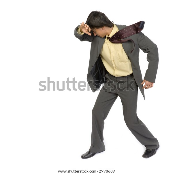 Man's standing on strong wind. He's protecting his face by hand. Isolated on white in studio.