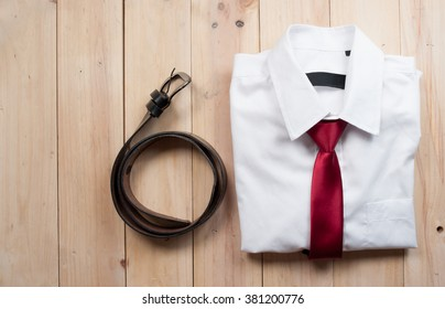 Man's style accessories,shirt with a bright tie and a belt on wooden background