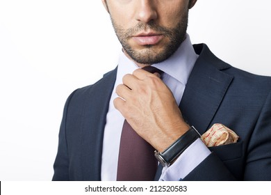 Man's style. dressing suit, shirt and cuffs. Fixing his tie.