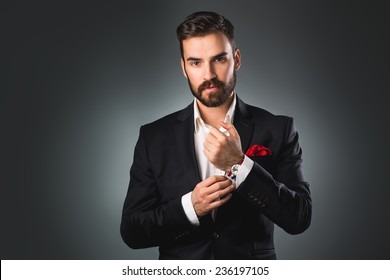 Man's style. Elegant young man getting ready. Dressing suit, shirt and cuffs